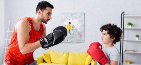 Photo pour Fils musulman en gants de boxe debout près du père pendant le travail à la maison, bannière - image libre de droit