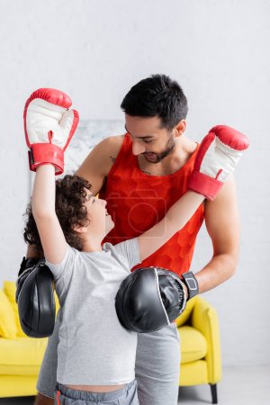 Photo for Arabian man standing near cheerful son in boxing gloves at home - Royalty Free Image
