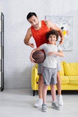 Photo pour Joyeux fils et père musulman pointant vers le basket-ball à la maison - image libre de droit