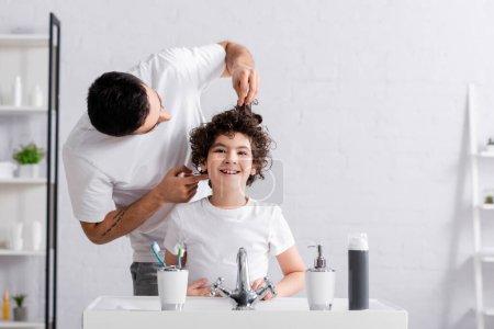 Photo pour Garçon joyeux debout près du père musulman toucher les cheveux dans la salle de bain - image libre de droit