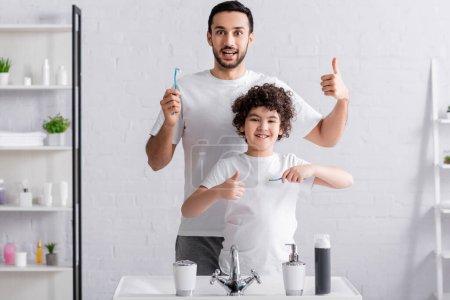 Photo pour Arabe fils et père montrant comme tout en tenant des brosses à dents dans la salle de bain - image libre de droit