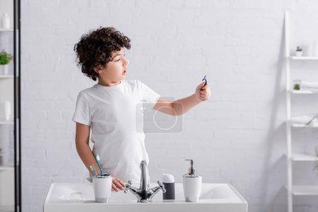 Photo pour Garçon musulman excité avec mousse à raser sur le nez en regardant le rasoir dans la salle de bain - image libre de droit