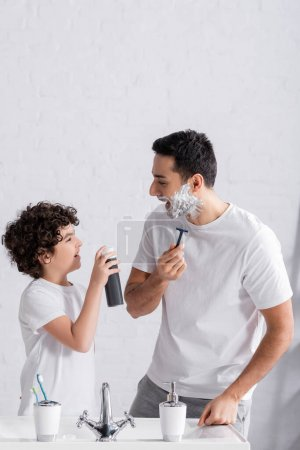 Photo for Smiling muslim boy holding shaving foam near father with razor and sink - Royalty Free Image