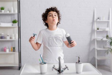 Photo pour Arabe garçon tenant mousse à raser et rasoir près de l'évier dans la salle de bain - image libre de droit