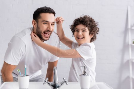 Photo pour Joyeux garçon arabe tenant une pince à épiler près du sourcil du père dans la salle de bain - image libre de droit