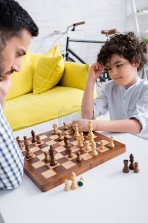 Photo for Arabian child looking at chess near father on blurred foreground in living room - Royalty Free Image