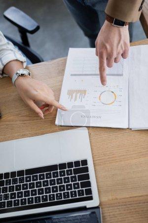 Vista recortada de gente de negocios apuntando al papel con letras analíticas y caracteres cerca de la computadora portátil