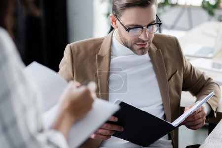 Businessman looking at documents near colleague with notebook on blurred foreground