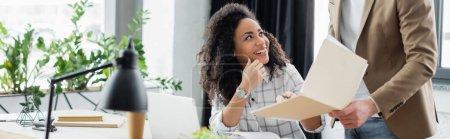 Photo pour Femme d'affaires afro-américaine assise près d'un homme d'affaires avec un dossier en papier au bureau, bannière - image libre de droit