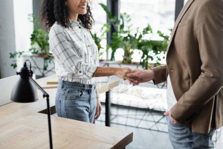 Photo pour Vue recadrée d'une femme d'affaires afro-américaine souriante serrant la main d'un collègue - image libre de droit
