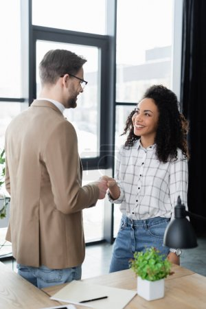 Photo for Smiling interracial business people shaking hands near paper folder in office - Royalty Free Image