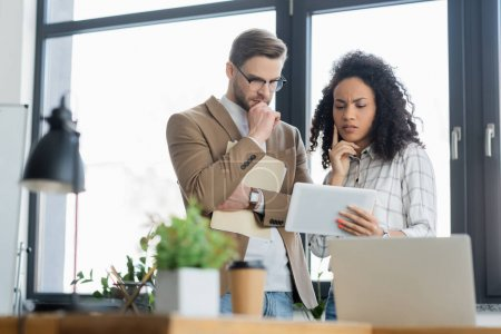 Photo for Pensive interracial business people looking at digital tablet near laptop and coffee to go on blurred foreground - Royalty Free Image