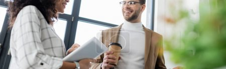 Smiling businessman with coffee looking at african american colleague with digital tablet, banner