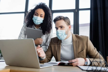 Photo for Businessman in medical mask pointing at laptop near african american colleague - Royalty Free Image