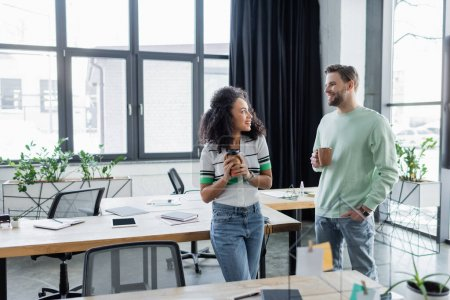 smiling interracial business colleagues holding coffee while talking in office