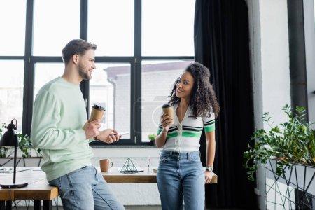 Photo pour Heureux partenaires d'affaires interracial debout avec café pour aller lors de la conversation au bureau - image libre de droit