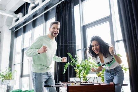 excited interracial business partners showing win gesture near table football