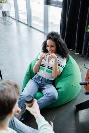 high angle view of laughing african american businesswoman sitting in bag chair near colleague