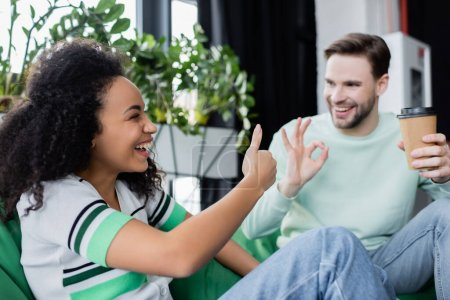 Photo for Happy interracial business partners showing okay and like gestures in office - Royalty Free Image
