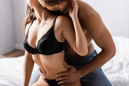 Photo for Man kissing sensual girlfriend in black bra on bed on blurred background - Royalty Free Image