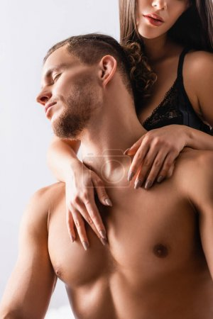 Mujer apasionada abrazando novio muscular con los ojos cerrados