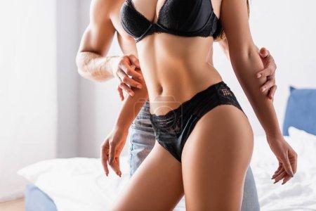 Ausgeschnittene Ansicht eines Mannes, der die Hände einer sexy Freundin in schwarzen Dessous im Schlafzimmer berührt