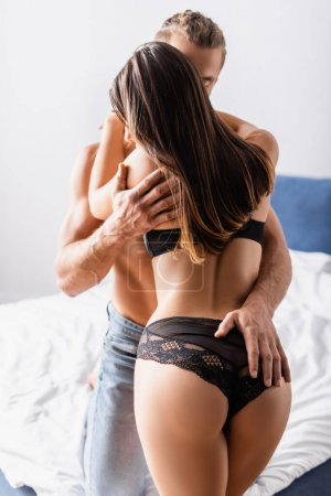 Photo for Young man touching buttocks of girlfriend in lingerie in bedroom - Royalty Free Image