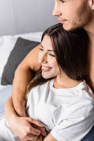 Young man hugging smiling girlfriend in t-shirt on bed