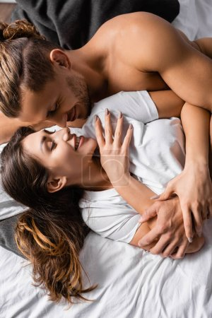 Top view of smiling woman in t-shirt lying near muscular man on bed