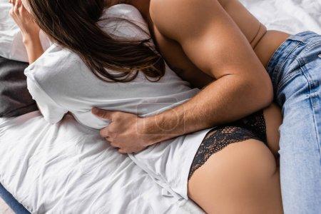 Ausgeschnittene Ansicht eines leidenschaftlichen Mannes, der Freundin in T-Shirt und Höschen auf dem Bett umarmt