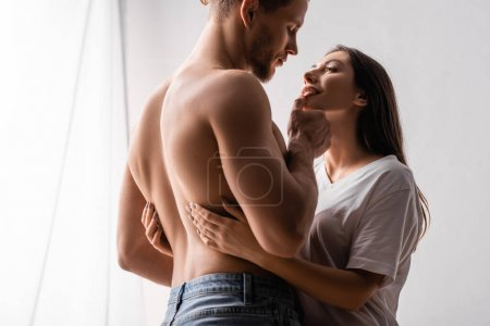 Shirtless man looking at sexy girlfriend in t-shirt at home