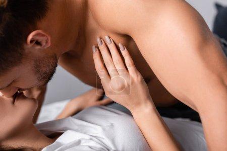 Photo pour Homme sexy embrasser petite amie en t-shirt sur le lit - image libre de droit