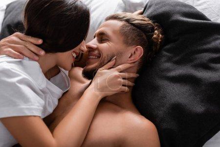 Photo pour Jeune femme en t-shirt embrasser petit ami souriant sur le lit - image libre de droit