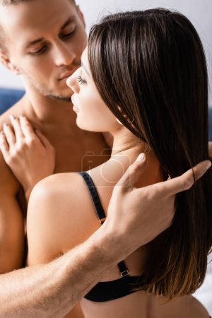Man touching hair of sexy woman in bra at home