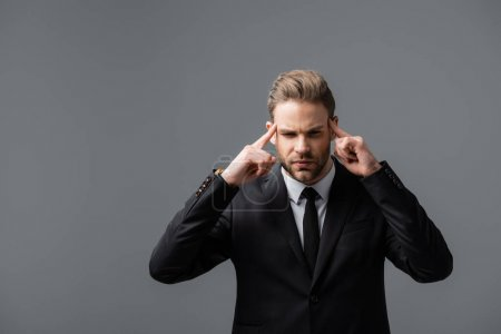serious businessman touching head while thinking isolated on grey
