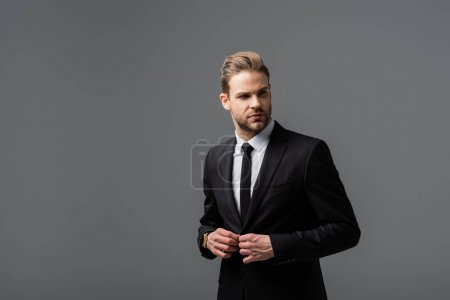 young businessman buttoning blazer while looking away isolated on grey
