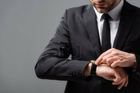 cropped view of businessman checking time on wristwatch isolated on grey