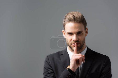 Photo pour Jeune homme d'affaires montrant signe de silence tout en regardant la caméra isolée sur gris - image libre de droit