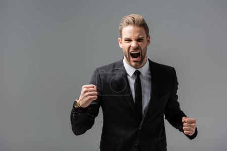 irritated businessman screaming and showing clenched fists isolated on grey