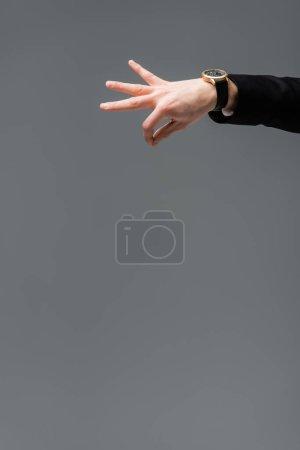 Teilbild eines Geschäftsmannes in Armbanduhr, der etwas mit Fingern auf grau isoliert hält