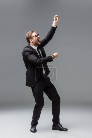 full length view of angry businessman with clenched fists screaming on grey