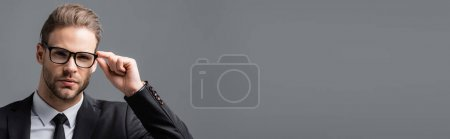 young, serious businessman adjusting eyeglasses while looking at camera isolated on grey, banner