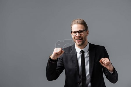 excited businessman in eyeglasses showing success gesture isolated on grey