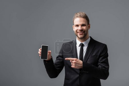 cheerful businessman pointing at smartphone with blank screen isolated on grey