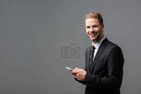 positive businessman smiling at camera while chatting on smartphone isolated on grey