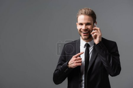 laughing businessman pointing at smartphone during conversation isolated on grey