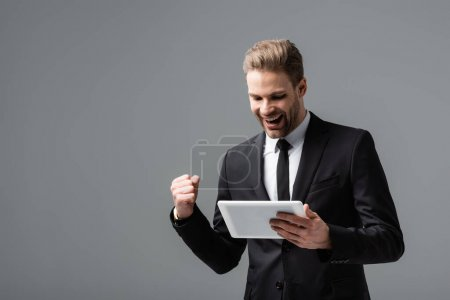 excited businessman showing win gesture while holding digital tablet isolated on grey