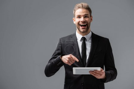 excited manager pointing at digital tablet while looking at camera isolated on grey