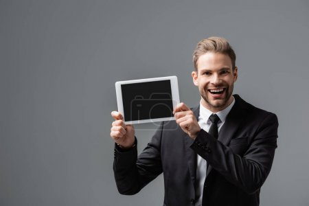 cheerful corporate manager showing digital tablet with blank screen isolated on grey
