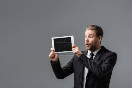 shocked businessman with open mouth showing digital tablet with blank screen isolated on grey